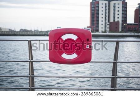 Lifebuoy hanging on fence - stock photo