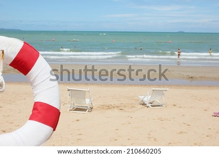 Lifebuoy hanging on pole at the beach  in Thailand - stock photo