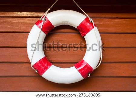 Lifebuoy hanging on wood wall - stock photo