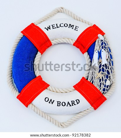 Lifebuoy on a white wall. A view of an lifebuoy or rescue device on a white wall. - stock photo