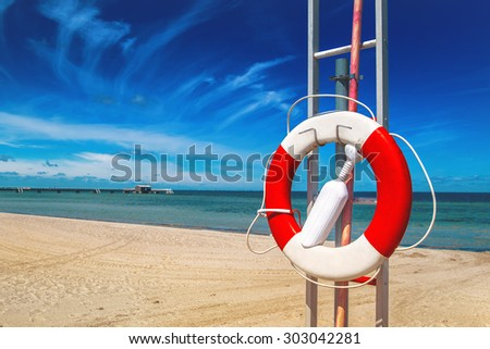 Lifebuoy, Red and White Life Preserver on Sandy Beach of Coastal Summer Vacation Resort - stock photo