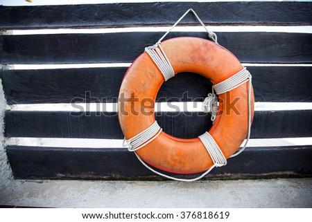 Lifebuoy ring on wooden railing  - stock photo