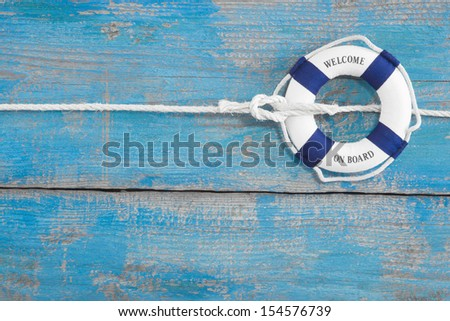 Lifebuoy tied with a rope - blue background for cruising - stock photo