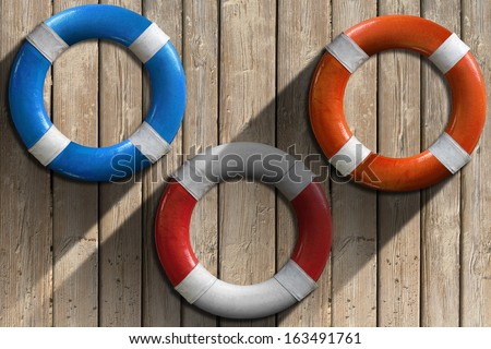Lifebuoys on Wooden Wall with Sand / Three lifebuoys hanging to a wooden wall with sand and shadows - stock photo