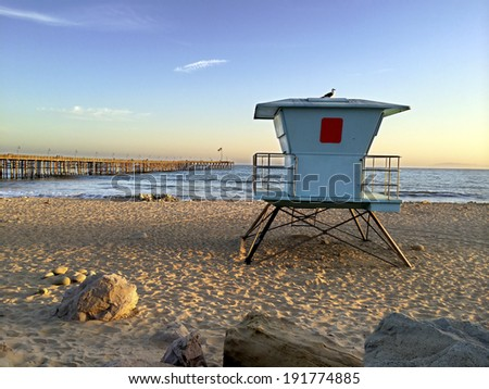 Lifeguard booth towering above sand near historic wooden pier, San Buenaventura, Southern California - stock photo