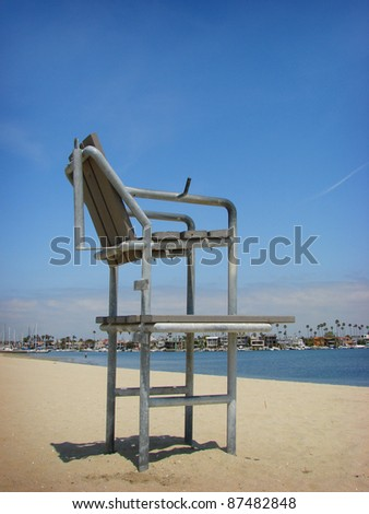 lifeguard chair on beach sand with water in background - stock photo