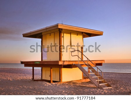 Lifeguard house in Hollywood Beach Florida during summer sunrise with calm ocean water in the background - stock photo