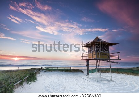 lifeguard hut on australian beach at sunrise with interesting clouds in background (gold coast, queensland, australia) - stock photo
