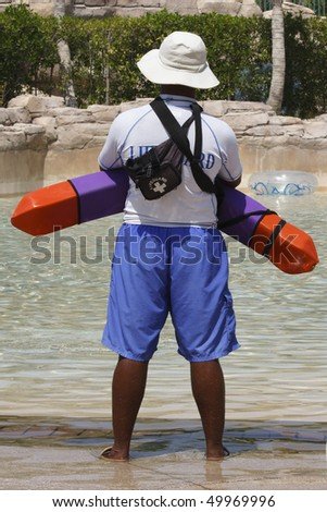 Lifeguard on duty in swimming pool - stock photo
