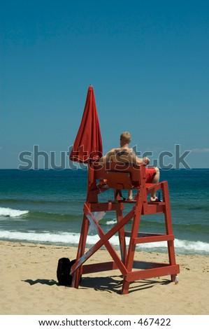 Lifeguard on duty on the beach. He has an interesting tattoo on his back and hand. Shot on Block Island beach, Rhode Island, USA - stock photo