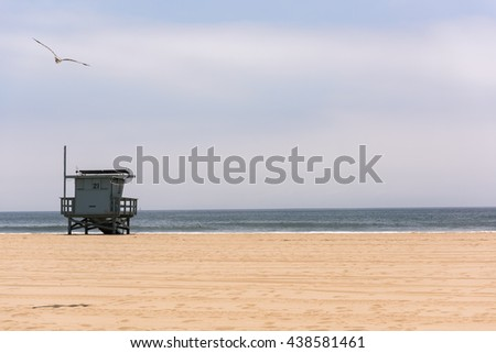 Lifeguard post and empty beach with a flying seagull in Venice Beach, Los Angeles, California - stock photo