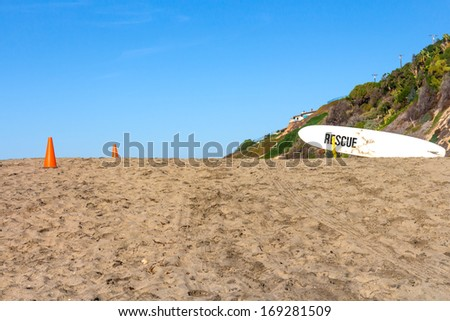 """Lifeguard rescue surfboard on sandy hill. White board with word """"rescue"""" on bottom. Orange safety cones on sand. Clear blue sky, hill background. Horizontal beach scene. - stock photo"""