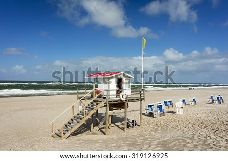 "Lifeguard station at Westerland on the island of Sylt, Schleswig-Holstein, Germany. Sign says ""Danger to life - swimming only with supervision"" in German. - stock photo"