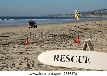 Lifeguard surfboard and surf patrol vehicle on a beach; Mission Beach; San Diego, California - stock photo