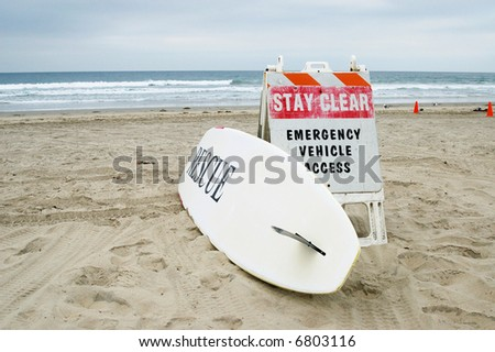 Lifeguard surfboard and warning sign; Mission Beach; San Diego, California - stock photo