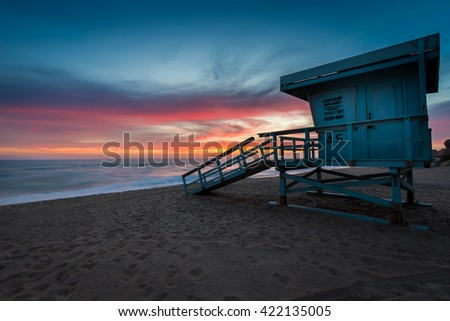 Lifeguard Tower on the Beach at Sunset with Rainbow Clouds in the Sky. - stock photo