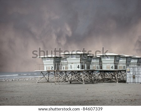 lifeguard towers on beach with storm clouds - stock photo