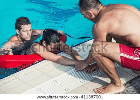 Lifeguards in training - Rescuing victim from public swimming pool - stock photo