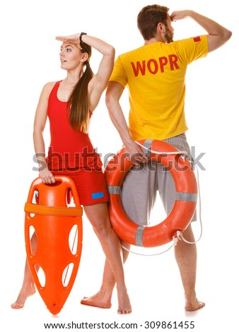 Lifeguards with rescue tube and ring buoy lifebuoy. Man and woman supervising swimming pool looking out into the distance. Accident prevention. - stock photo
