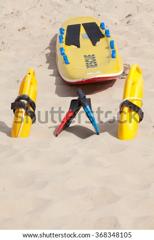 Lifesaving raft, floatation devices and swimming fins lying on beach in summer sun - stock photo