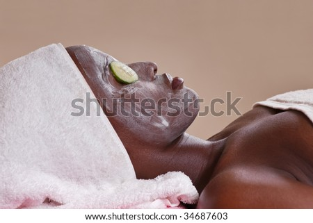 lifestyle, african american woman having a facial treat at the spa - stock photo