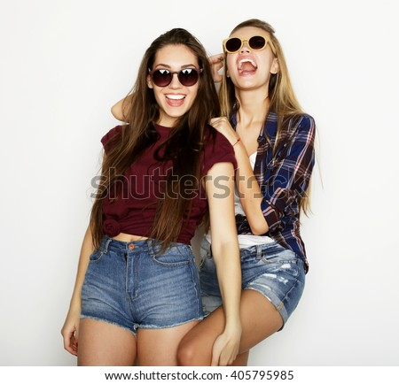 lifestyle and people concept: Two young girl friends standing together and having fun. Looking at camera.