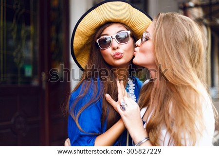 Lifestyle bright trendy portrait of two elegant hipster girls having fun together, stylish outfits, happy smiling faces, bright colors. Kissing to the cheek and hugs, joy, positive, love, friendship.  - stock photo