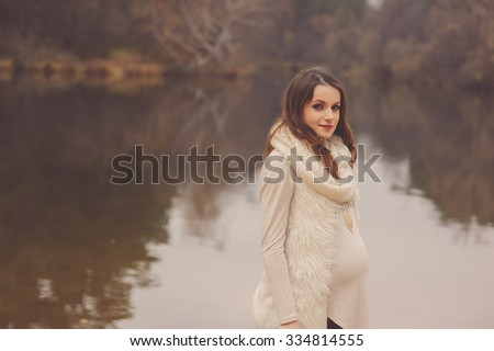 lifestyle capture of beautiful young pregnant woman walks outdoor, soft warm toned, cozy mood, soft focus - stock photo