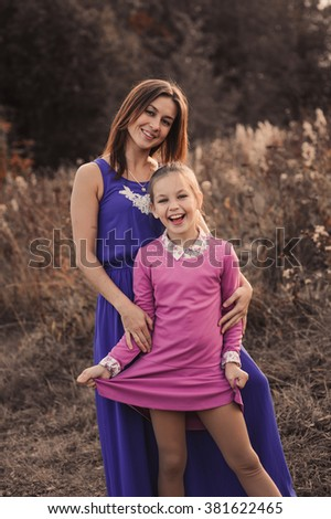 lifestyle capture of happy mother and preteen daughter having fun outdoor. Loving family spending time together on the walk. Cozy weekend.