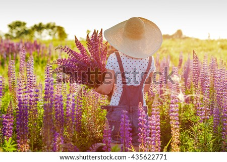 lifestyle concept - beautiful happy woman enjoying fresh air in lupines flower field - stock photo