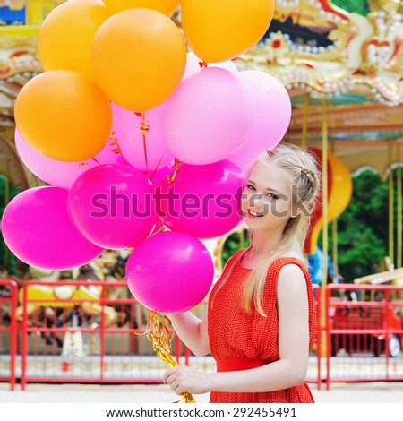 Lifestyle concept, happy young woman holding colorful latex balloons in the amusement park in front of the carousel
