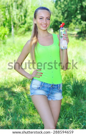 Lifestyle concept with beautiful fit woman holding a bottle of refreshing water