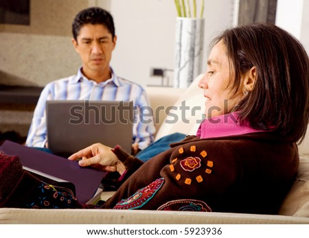lifestyle couple at home where she is reading while he is on the laptop computer - stock photo