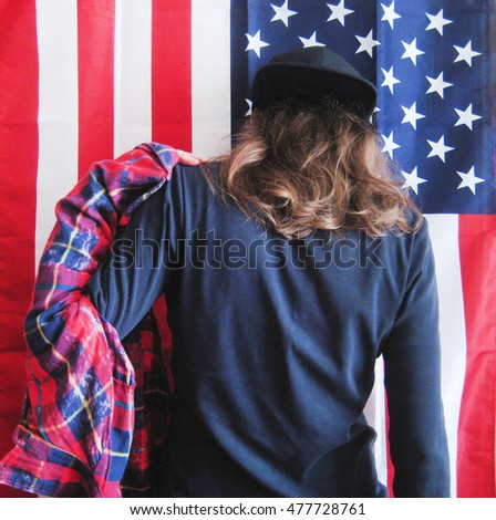 Lifestyle cropped portrait of young hipster girl dressing putting on plaid red shirt getting ready to go out. Casual clothes black pullover and snapback cap with hair down on american flag background