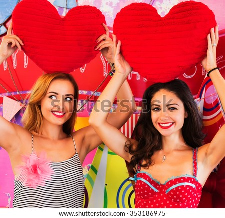 Lifestyle fashion close up portrait of two cheerful pretty girls best friends having fun in the mall in Christmas time. Smiling, shopping and and keeping overhead large toy hearts. Bright make up