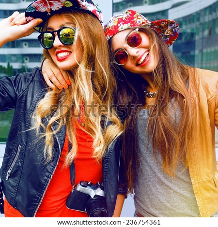 Lifestyle fashion portrait of happy stylish girls friends, hugs and enjoy travel time together, wearing hats and sunglasses holding vintage retro camera, bright colors positive emotions. - stock photo