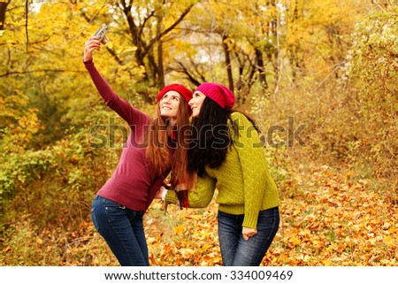 Lifestyle fashion portrait of happy stylish girls friends. Two cute girls sisters taking pictures in nature at the autumn park. - stock photo