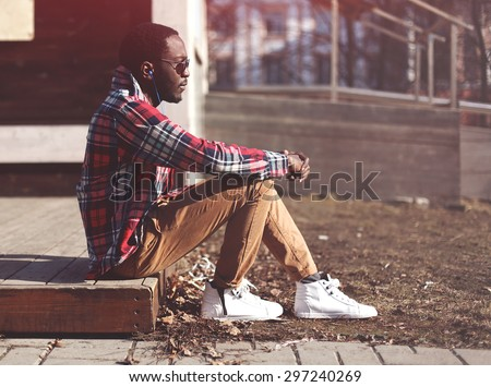 Lifestyle fashion portrait of stylish young african man listens to music evening and enjoys sunset, wearing a hipster plaid red shirt and sunglasses sitting in profile outdoors  - stock photo