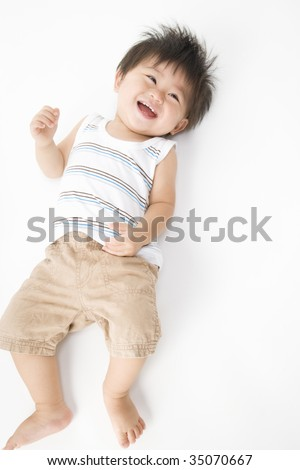 LIFESTYLE IMAGE-a lovely smiling baby lying on the floor - stock photo