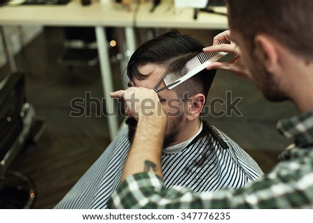 Lifestyle image. Client during a visit to the hair cutting Barbershop. Stylist-barber cuts her hair with scissors stylish man with a beard and mustache. - stock photo