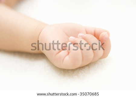 LIFESTYLE IMAGE-close-up shot of a tiny hand of baby