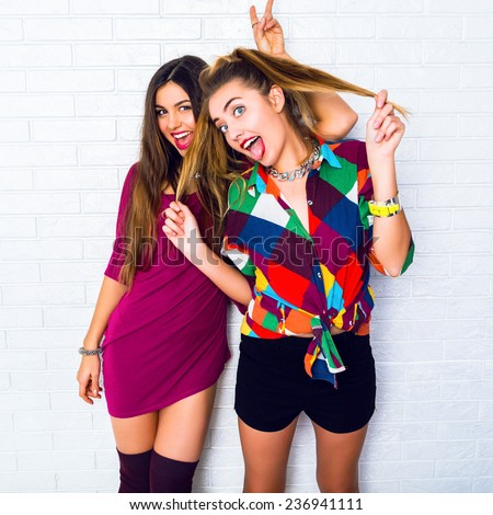 Lifestyle image of two young friend girls making crazy funny faces, wearing bright hipster clothes, urban white background. Showing tongue and screaming. - stock photo