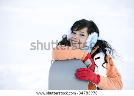 Lifestyle image of  young adult  snowboarder girl - stock photo