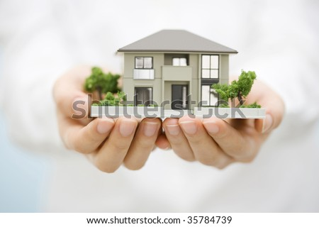 LIFESTYLE IMAGE-the model house with woman's hands isolated on white - stock photo