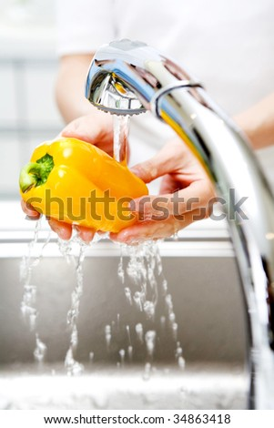 LIFESTYLE IMAGE-woman's hands washing a yellow paprika - stock photo