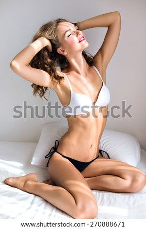 Lifestyle indoor fashion portrait of woman with amazing slim fit sexy body, posing on the bed in morning time, wearing simple casual lingerie, relax and enjoy sunny day. - stock photo