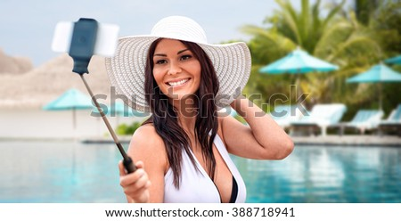 lifestyle, leisure, summer, technology and people concept - smiling young woman or teenage girl in sun hat taking picture with smartphone on selfie stick over beach and swimming pool background - stock photo