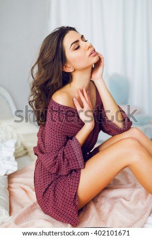 Lifestyle morning image of young fresh woman in sexy bathrobe  sitting and relaxing on her bed, enjoying lazy day. Sensual girl with perfect body.  - stock photo