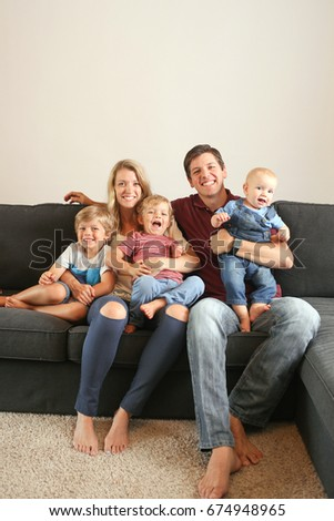 Lifestyle of adorable young family at home on the couch