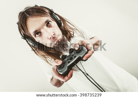 Lifestyle of young people. Student man spending time on playing games videogames console. Long haired guy focus on gaming. - stock photo